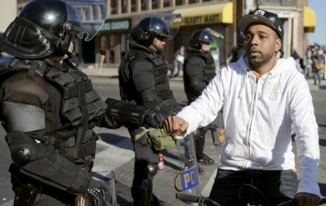 Man fist bumps law enforcement personnel during Baltimore protests. Courtesy of USAtoday.com
