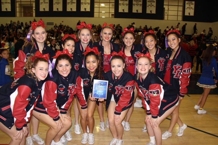 Varsity cheer shows off their first place award.