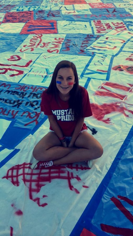 Katelyn demonstrates school spirit during rivalry week, by sitting on the poster covered quad which she helped produce.