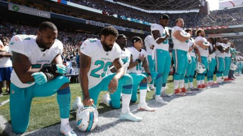 Arian Foster, Michael Thomas, Kenny Stills, and Jelani Jenkins from the Miami Dolphins take a knee during the National Anthem.