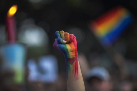 A fist raises in defiance at a vigil for the victims of the Orlando shooting.