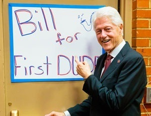 Bill Clinton stands next to a poster with the humorous suggestion of