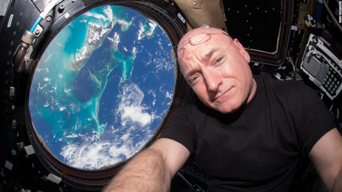 Kelly poses with his astonishing view of Earth, with just a month left on his journey in the vast world of space.