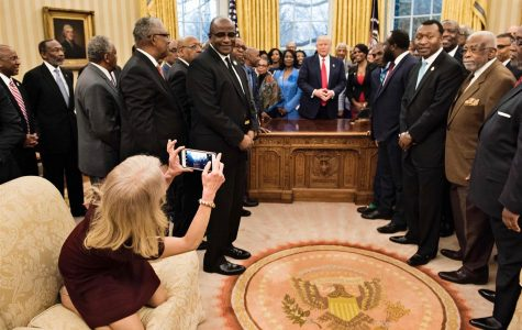 Kellyanne Conway is sitting improperly on the couch while taking a photo of the important educators and the president.