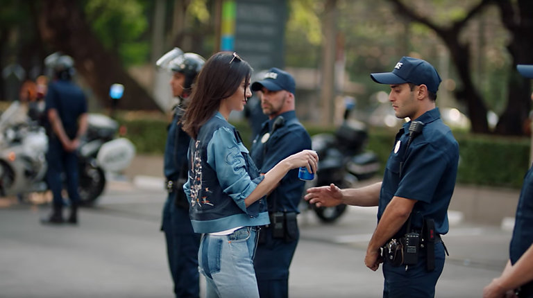 Kendall Jenner hands a police officer a Pepsi, easing the tension between the protesters and the law.