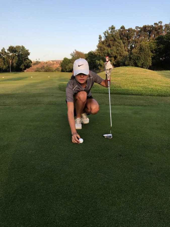 Olivia Yerkes focuses on the green while she gets ready to putt the ball.