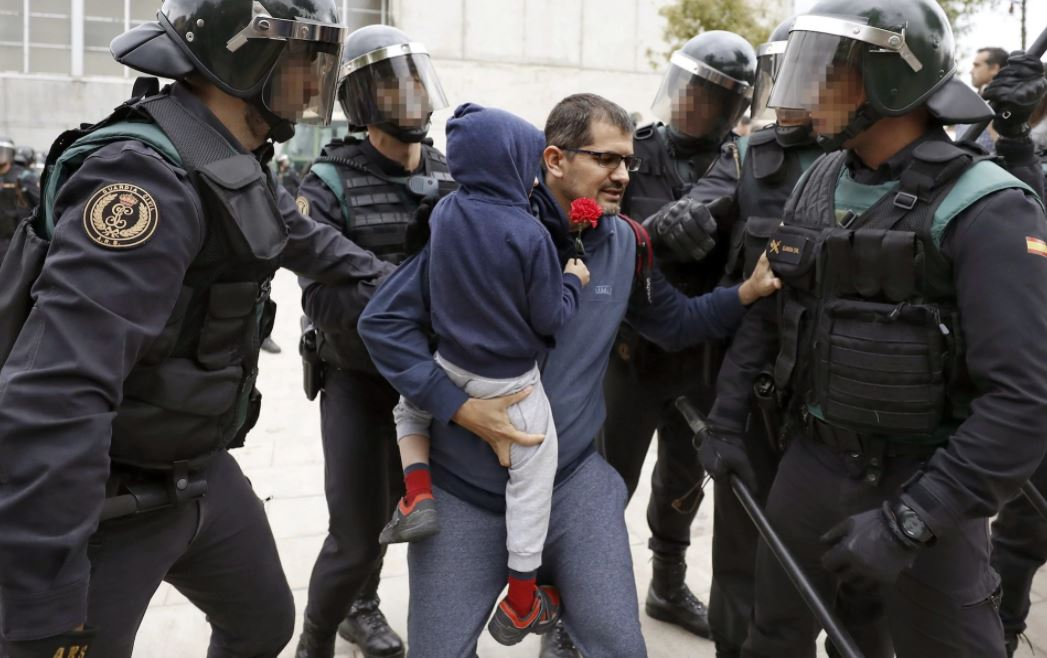 A Catalan man carrying a child is evicted from a school by the police.