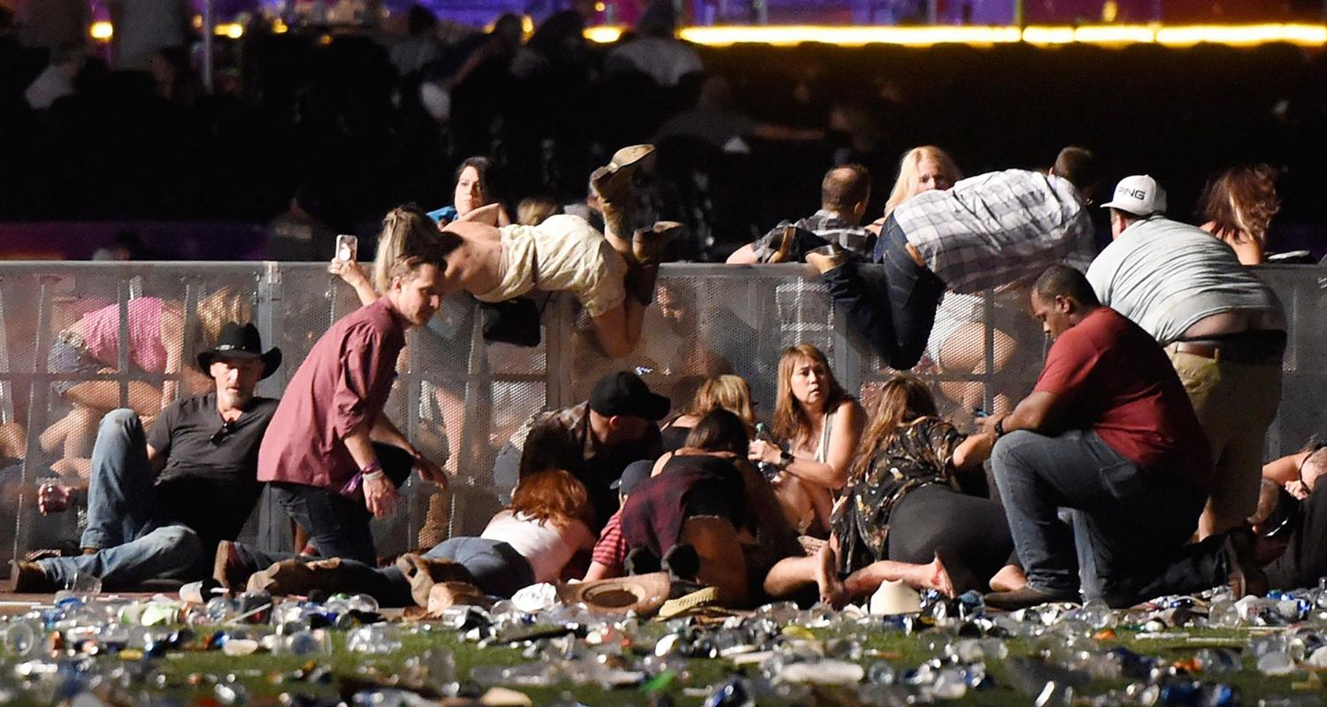 Concert attendees climb over fences to escape the gun fire.