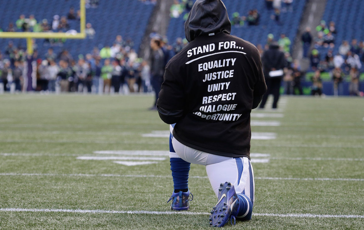 Above, an Indianapolis Colts player Kneels while stretching to display the team message and unity in which their team is trying to showcase.