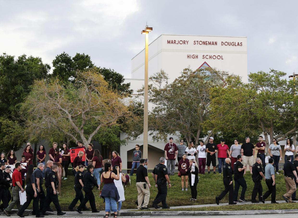 The photo is taken two weeks after the shooting that took place at Marjory Stoneman Douglas High School. Students bring posters and flower to commemorate those who were lost.