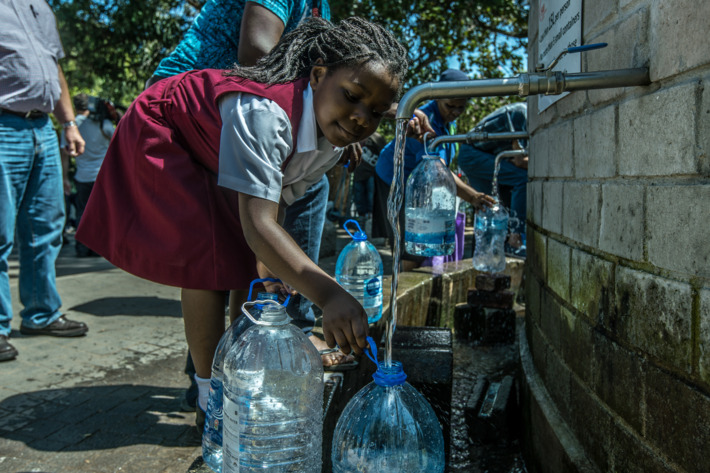 A little girl is seen refilling jugs of water for not only her but for her whole family as well.