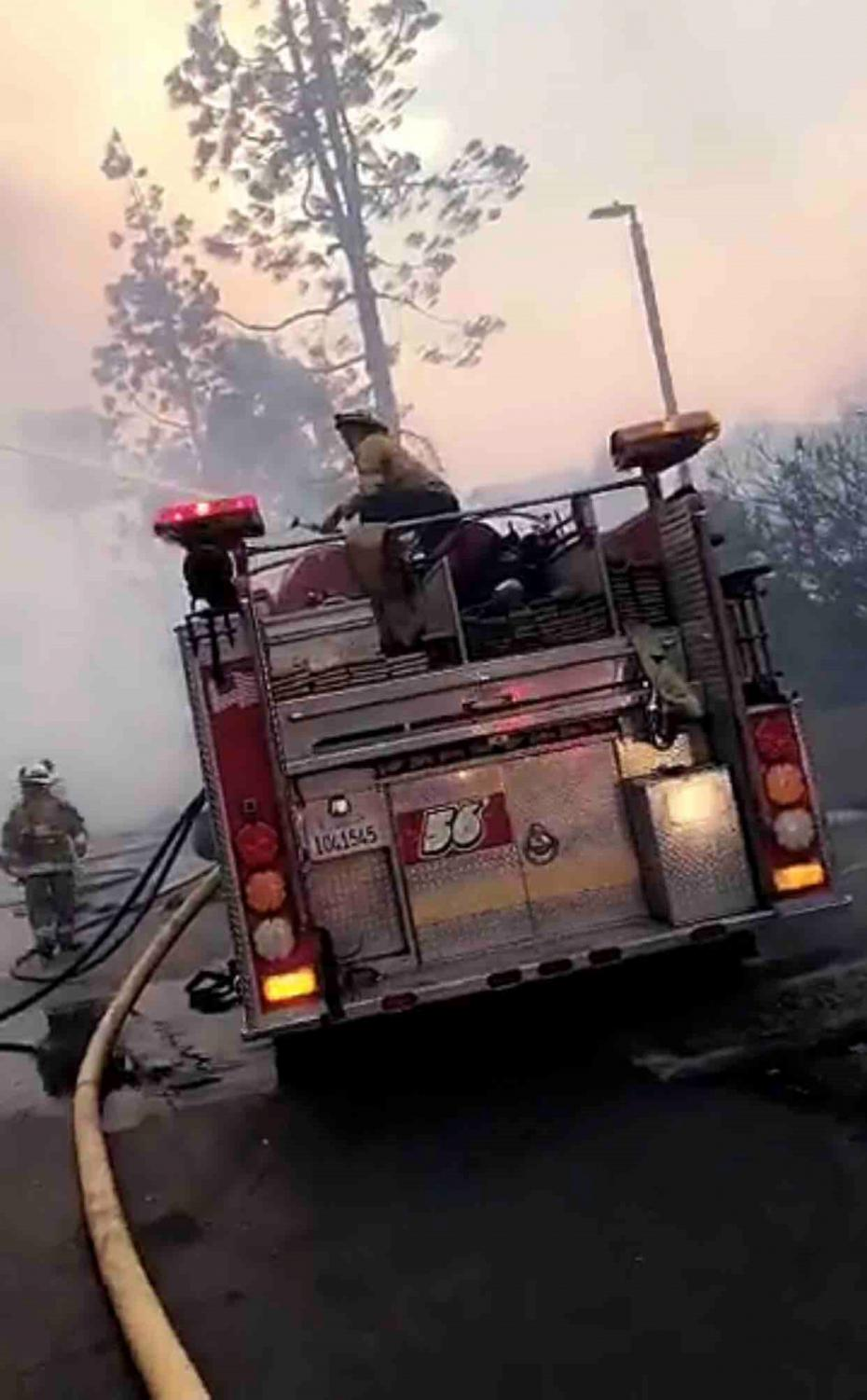 Firemen in a neighborhood that was burnt and continue to put out the remaining flames.