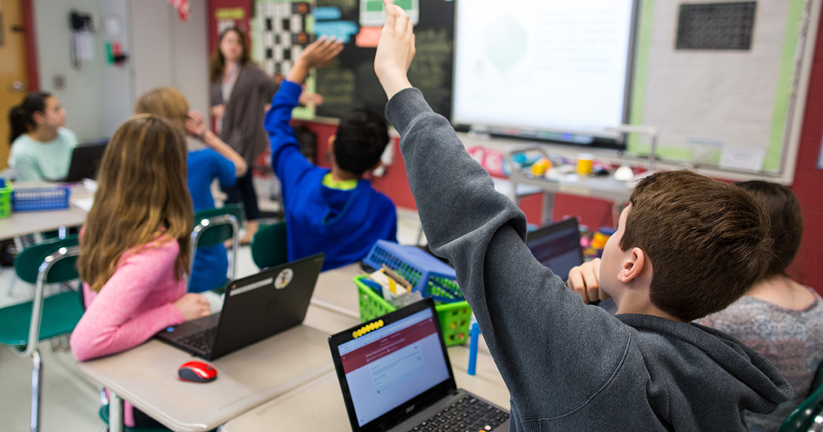 Students raise their hands during a class discussion.  Photo credits to Google For Education.