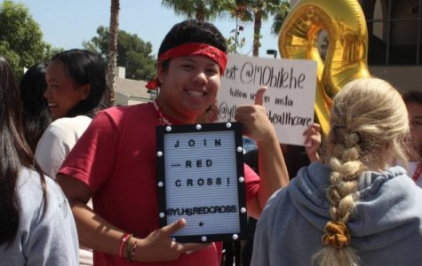 Stephen Serrano (11) holds up a sign trying to promote his club.