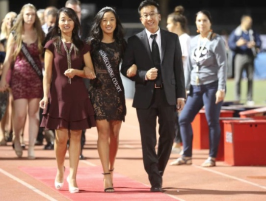 Lauren Bui (12), Yorba Linda High School's Homecoming Queen, struts down the red carpet with her parents at the halftime reveal.