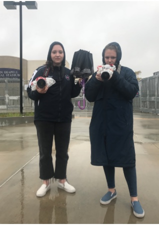 Due to the rain, Savannah Pietsch (11) and Riley Pietsch (10) had to cover up the cameras in order to get the perfect shot.
