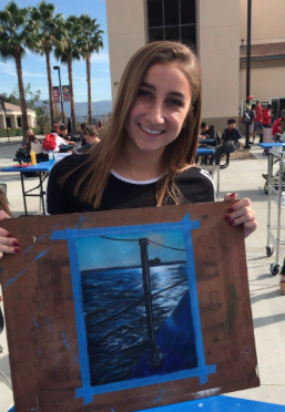 Natalie Windawi (11) shows off her visual arts piece in the quad at lunch.