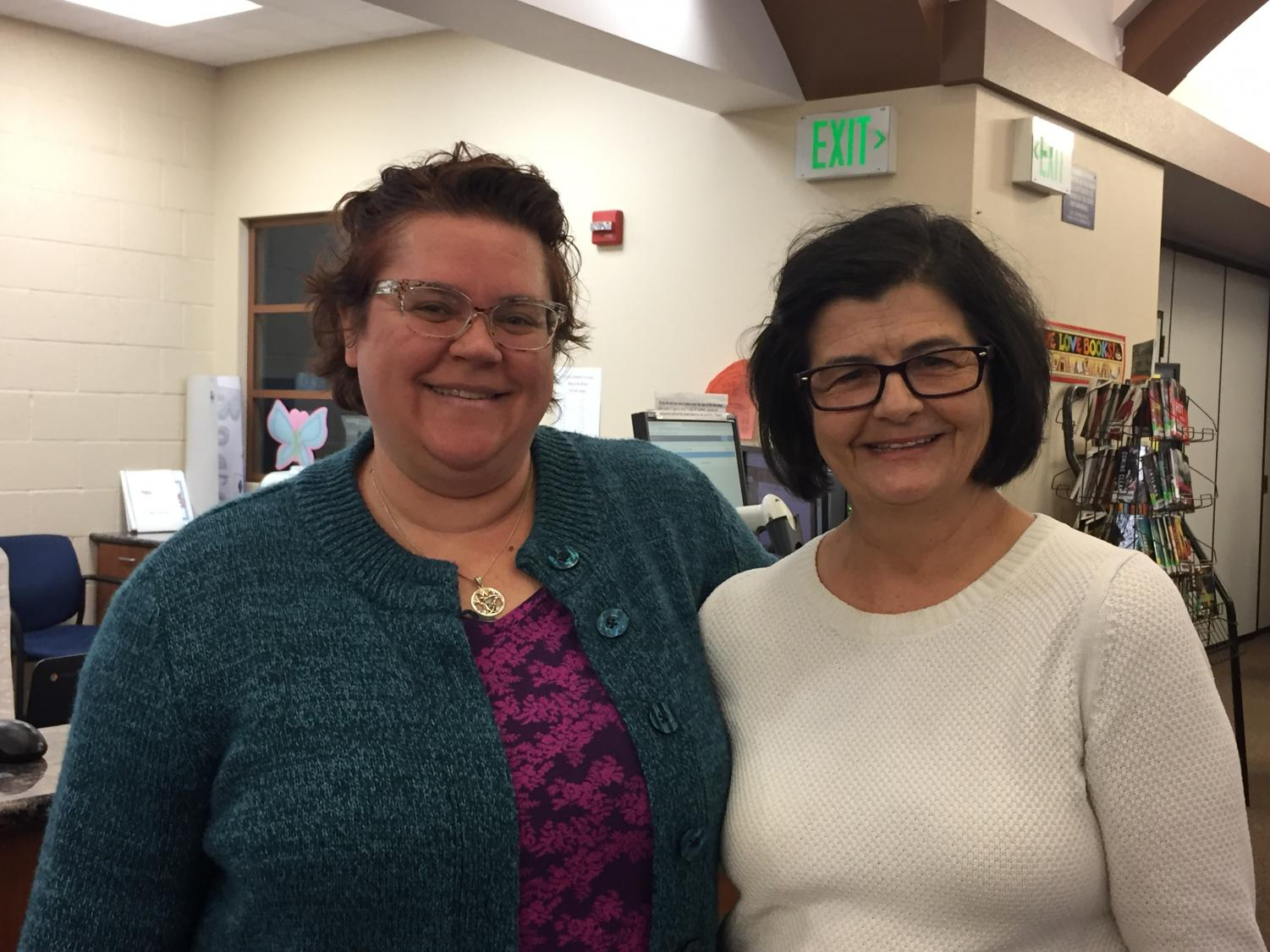 Mrs. Phillips and Mrs. Yoshinaga in their natural habitat: the forest of books!