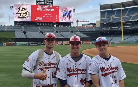 Players from the baseball team pose proudly in front of the