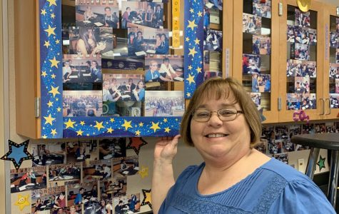 Ms. Luxa smiles with a gallery of pictures from her first class of teaching at YLHS.