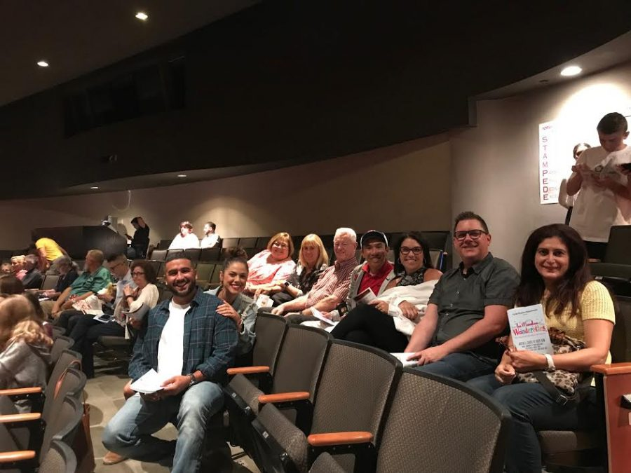 A number of YLHS teachers and staff sit together with large smiles spread across their face, excited to watch the Fall musical.