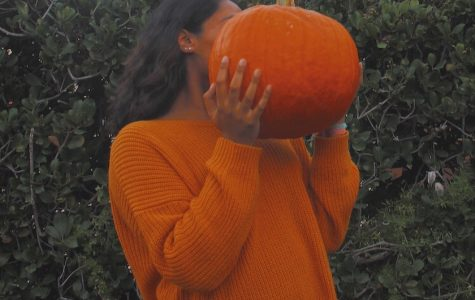 Halloween color themed photo of Karina Shah with a pumpkin.