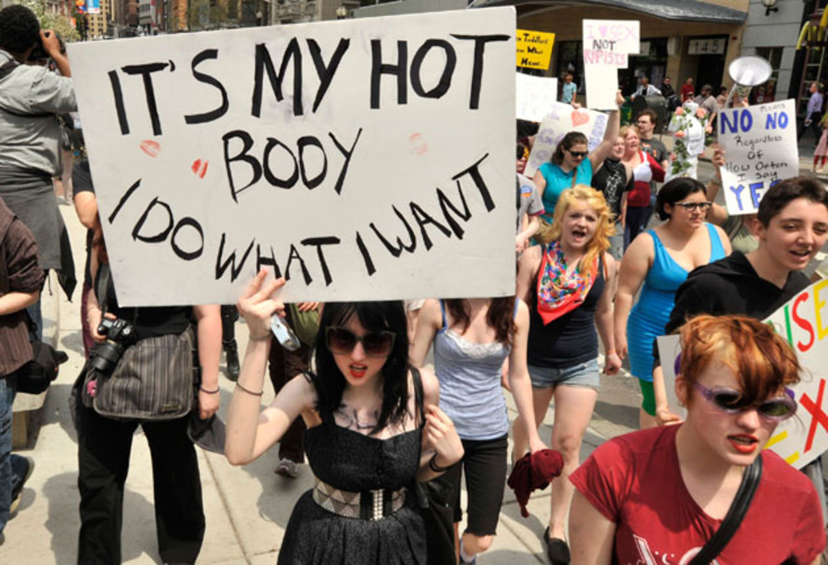 An image taken from a protest in which a woman writes,
