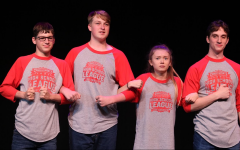 (From left to right) Michael Vino (11), Maxwell Greene (10), Alyssa Van (10), and Riley Pietenpol (12) link arms during an intense game of Spelling Bee. They wait in anticipation for the audience to suggest the next word for them to spell.