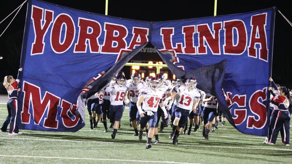 The YLHS Varsity Football team runs onto the field before a game.