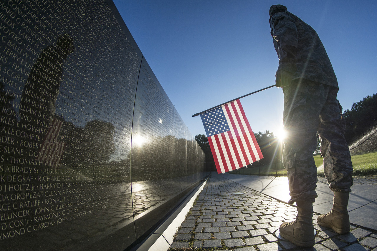 """At the Vietnam Veterans Memorial in Washington, D.C. an American soldier observes the names on """"The Wall"""" of the memorial."""