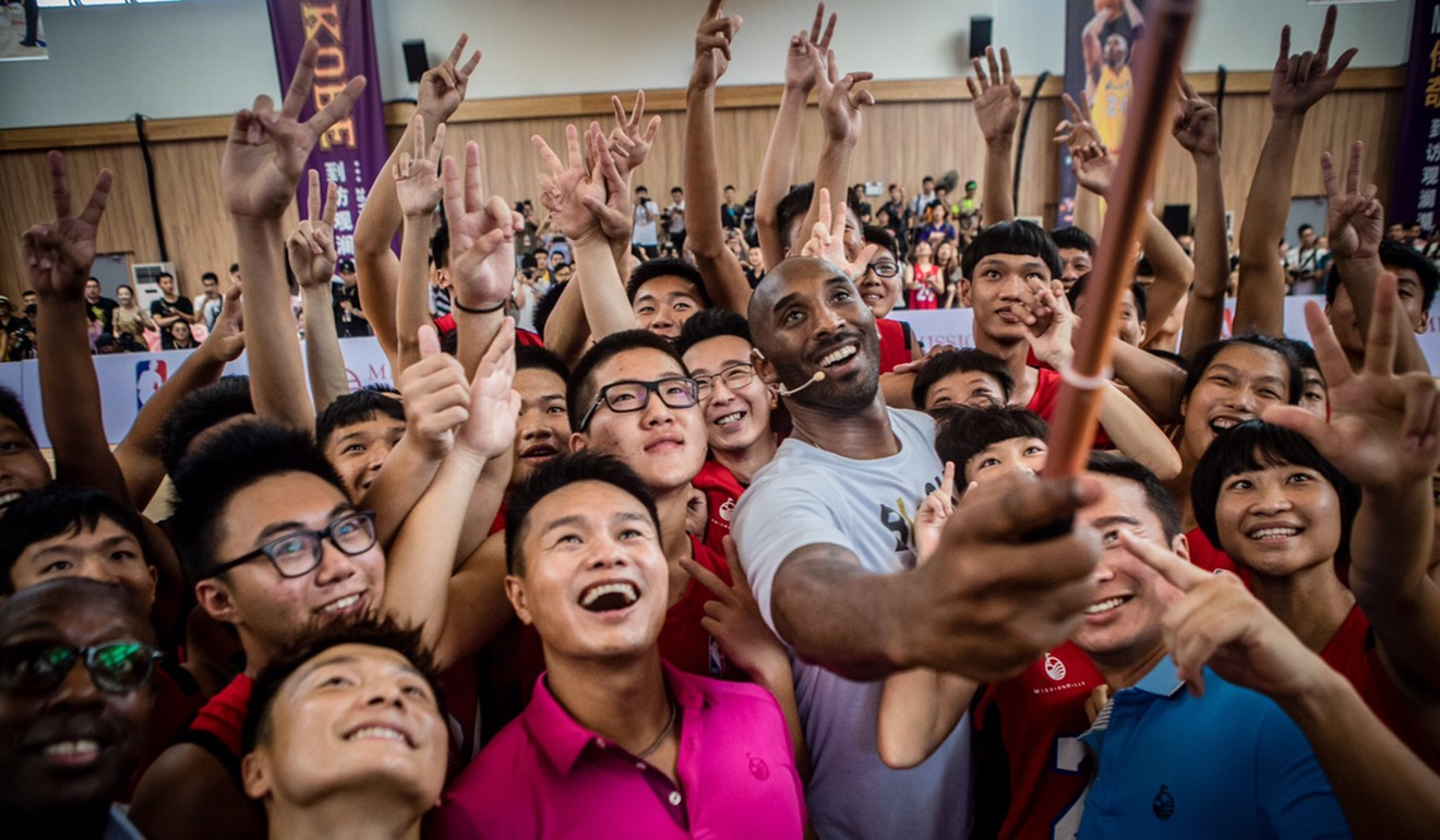 """Kobe takes a picture with some of his youth fans during the grand opening of his new """"basketball school"""" in Haikou, China, during 2017."""