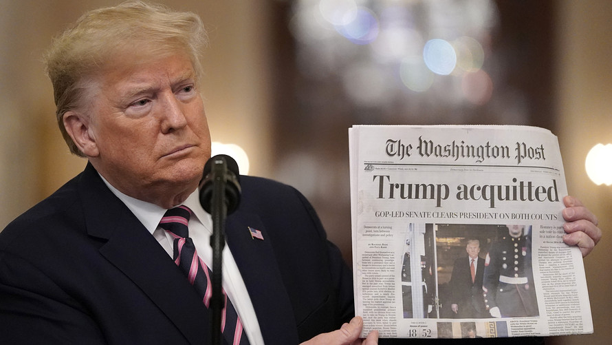 President Trump holds up a newspaper article declaring his acquittal on both counts of impeachment.