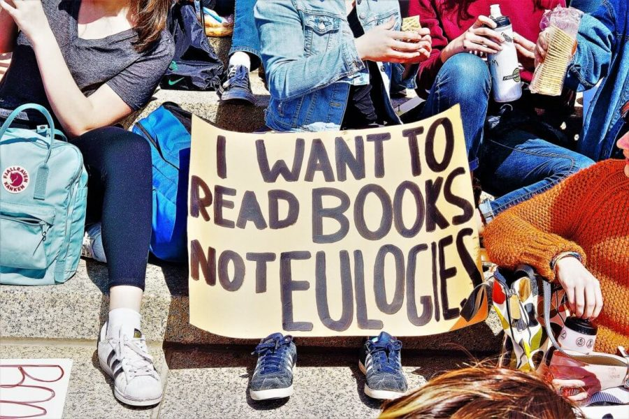 Students hold a sign explaining that they rather read books than eulogies. They're aware of this issue, and they demand change.