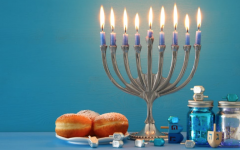 A picture of a fully lit menorah alongside sweets and dreidels for a full Hanukkah setting.