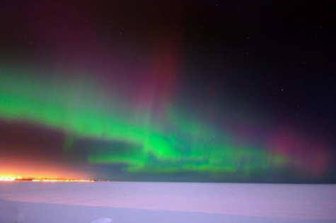 The Northern Lights glimmer in red, purple, and green over a frozen Lake Superior in Michigan.