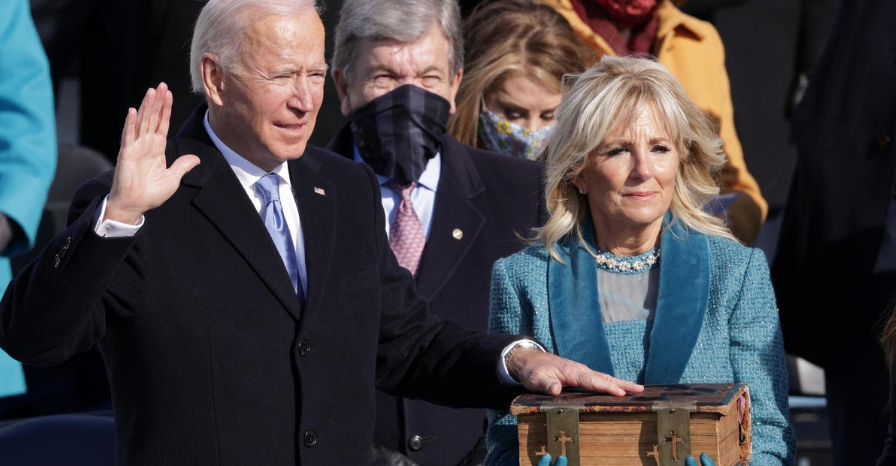 Joe Biden places his hand on his 128-year-old family Bible alongside his wife, Jill Biden, as he recites the oath of office to confirm his role as 46th President of the United States.