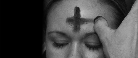 A priest finishes the shape of a cross over this young women
