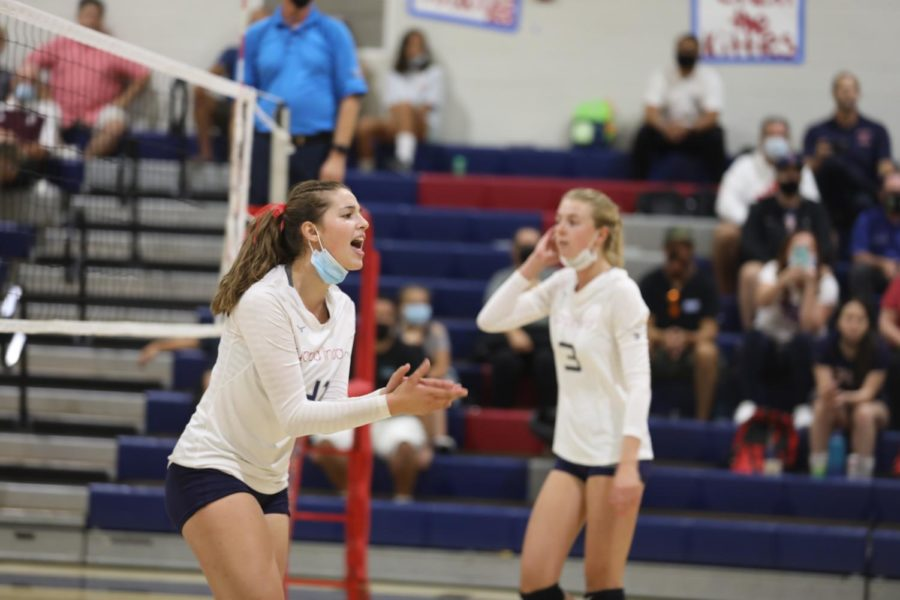 Kate Jacobsen (11) is cheering on her fellow teammates to help them stay energetic and hardworking during the match to win the biggest game for YL volleyball
