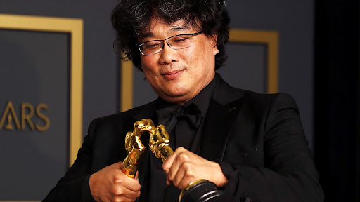 """Director Bong Joon Ho poses with two of his three Oscars at the 2020 awards show in the dubbed """"Oscar Kiss"""" moment."""